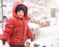 Babyjongen met rode jasje en hoed terwijl sneeuw Stock Afbeeldingen