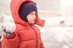 Babyjongen met sneeuwbal terwijl het sneeuwen Stock Afbeelding