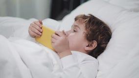 Babyjongen met tablet die haar ogen na het schreeuwen wrijven Hij ligt op het bed, houdend een gele smartphone in zijn handen stock footage