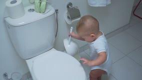 Babyjongen met toilet schoonmakende borstel stock video
