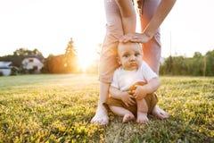 Babyjongen met zijn moeder buiten in de tuin stock afbeeldingen