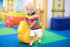 Babyjongen op schommeling bij de ruimte van het opvangspel Jonge geitjesspel royalty-vrije stock foto's