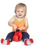 Babyjongen in sinaasappel, die met rode bokshandschoenen zitten. stock foto's