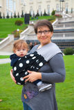 Babyjongen in slinger in moederswapens Royalty-vrije Stock Afbeelding