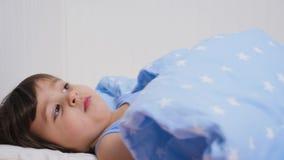 Babyjongen twee jaar het oude liggen in bed stock videobeelden