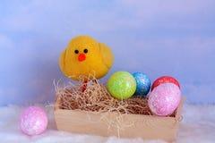 Babyküken mit bunten Eiern in der Front lizenzfreie stockfotos