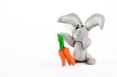Babykaninchen und Karottenstatue auf Weiß lizenzfreie stockfotos