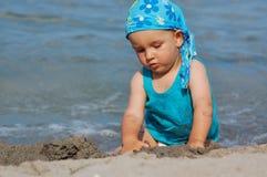 Babykind, das in den Wellen spielt Stockbild