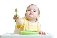 Babykind, das im Stuhl und in ausstreckendem a sitzt Stockfotografie