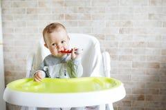 Babykind die met lepel in zonnige keuken eten Portret van gelukkig jong geitje als hoge voorzitter De ruimte van het exemplaar royalty-vrije stock foto's