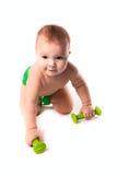 Babykind, Kleinkind in den grünen Windeln, die Übungen mit dumbbel tun Stockbilder