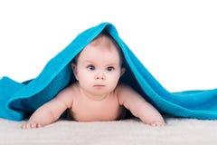 Babykind met grote ogen onder blauwe handdoek Royalty-vrije Stock Foto