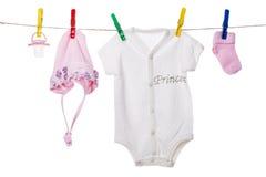 Babykleidung, die an der Wäscheleine hängt Stockbilder