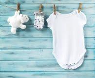 Babykleidung und weißer Bär spielen auf einer Wäscheleine