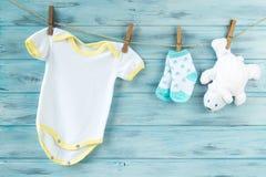 Babykleidung und weißer Bär spielen auf einer Wäscheleine Stockbild