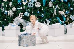 Babykleinkind im weißen Kleid kleidet mit Geschenkpräsentkarton durch Baum des neuen Jahres Lizenzfreie Stockfotos
