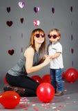 Babykleinkind mit Mutter im Studio, welches das lächelnde Lachen der lustigen Gläser trägt, Spaß habend Stockbilder