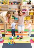 Babykleinkinder, die mit bunten pädagogischen Spielwaren zusammen mit Müttern im Kindertagesstättenraum spielen stockbilder