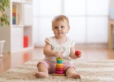 Babykleinkindm?dchen, das mit h?lzernen Spielwaren spielt und Spa? hat lizenzfreies stockfoto