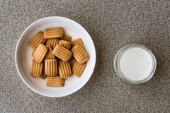 Babykoekje met melk in witte kom Stock Afbeeldingen