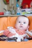 Babyleeftijd van 5 maanden die op highchair zitten Royalty-vrije Stock Foto's