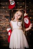 Babymeisje 4-5 éénjarigen die in ruimte over Kerstmisboom stellen met decoratie het bekijken camera Vrolijke Kerstmis Het dragen  Royalty-vrije Stock Fotografie