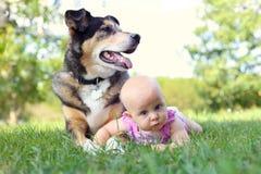Babymeisje die buiten met Huisdierenduitse herder Dog leggen royalty-vrije stock foto