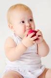 Babymeisje die een appel bijten Royalty-vrije Stock Afbeeldingen