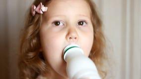 Babymeisje die een melkdrank van een fles, kefir, zuivelproduct drinken Kind die en een witte snor glimlachen tonen van stock footage