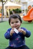 Babymeisje die een snack eten Stock Afbeeldingen