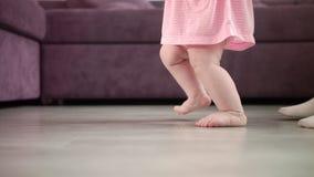Babymeisje die eerste stappen in haar leven doen Zuigeling het leren gang Kleine voeten stap stock video