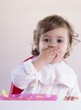 Babymeisje die fruit met haar handen eten Stock Fotografie