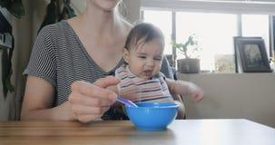 Babymeisje die haar eerste beet van voedsel eten stock video