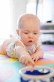Babymeisje die met blauwe ogen op mat bij vloer spelen Royalty-vrije Stock Foto's