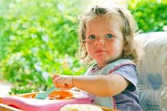babymeisje die met lepel eten stock afbeelding