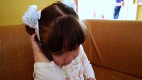 Babymeisje die onhandig op mobiele telefoon, langzame motie spreken stock videobeelden