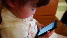 Babymeisje die onhandig op mobiele telefoon, langzame motie spreken stock footage