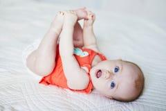 Babymeisje die op achter haar en wat betreft haar voeten liggen Stock Fotografie