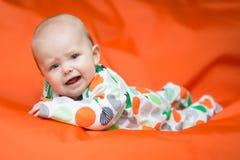 Babymeisje die op een buik op een oranje hoofdkussen liggen Stock Afbeelding