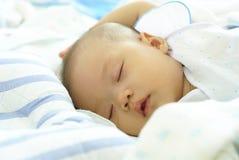 Babymeisje die op haar bed liggen De leuke baby in witte kleding glimlacht stock afbeelding