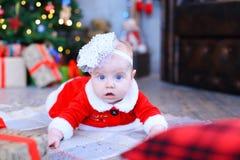 Babymeisje die op plaid liggen en camera in stu van het Nieuwjaar bekijken Stock Fotografie