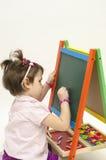 Babymeisje die op zwarte raad met krijt trekken Stock Fotografie