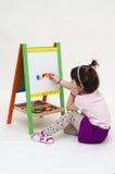 Babymeisje die op zwarte raad met krijt trekken Royalty-vrije Stock Afbeeldingen