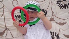 Babymeisje die pret hebben openlucht Groen en rood speelgoed in de hand van meisje stock footage