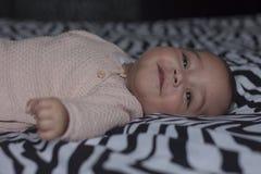 Babymeisje die in roze kleren op oudersbed lachen royalty-vrije stock afbeelding