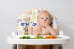 Babymeisje die ruw voedsel eten Stock Fotografie