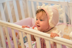 Babymeisje die zich in haar voederbak bevinden stock foto