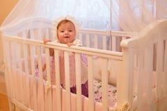 Babymeisje die zich in haar voederbak bevinden stock fotografie