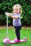 Babymeisje het berijden in de tuin op autoped stock foto's