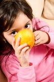 Babymeisje het drinken sap direct van een sinaasappel stock foto's